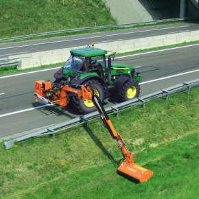 Zielony ciągnik John Deere kosi pobocze autostrady za pomocą pomarańczowej kosiarki bijakowej na wysięgniku Camel 900 firmy Samasz