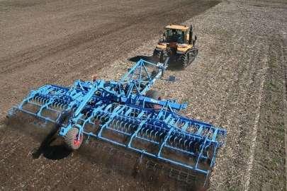 Niebieski agregat lemken cultivator z ciągnikiem Challenger uprawia pole przed siewem Korbanek.pl