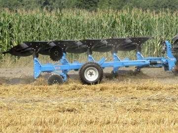 Pług obracalny ORKAN firmy Mandam na tle pola kukurydzy
