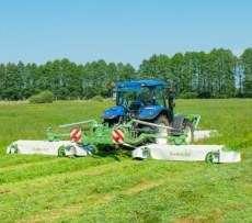 Niebieski traktor rolniczy z zestawem kosiarek MegaCUT firmy Samasz podczas koszenia trawy na łące