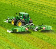 Kosiarki dyskowe GigaCUT firmy Samasz wraz z zielonym ciągnikiem rolniczym koszą trawę na łące