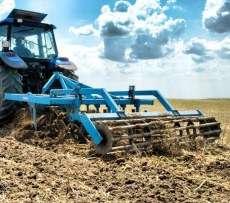 Kultywator gruber MANDAM typ KUS podczas pracy w polu na tle pierzastego nieba