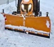 Pomarańczowy spychacz do śniegu City firmy Samasz zaczepiony do ciągnika komunalnego odśnieża chodnik
