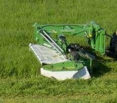 Zielona kosiarka czołowa dyskowa Samasz typ KDF podczas koszenia na łące