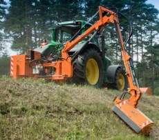 Pomarańczowa kosiarka wysięgnikowa bijakowa KWT firmy Samasz Białystok zawieszona na zielonym ciągniku kosi rów