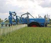 Niebieski opryskiwacz zaczepiany rolniczy firmy Lemken typ Primus wykonuje oprysk w zbożu Korbanek.pl