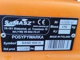 Pomarańczowa tabliczka znamionowa na czarnej posypywarce piasku i soli Samasz Sand 400