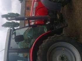 Ujęcie z boku na ciągnik rolniczy marki Massey Ferguson 5465 na tle gospodarstwa, kabina, koła, korbanek.pl
