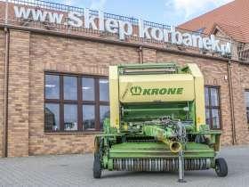 używana prasa zwijająca Krone Vario Pack 1500 Multi Cut widok od przodu szeroki podbieracz na tle sklepu części korbanek