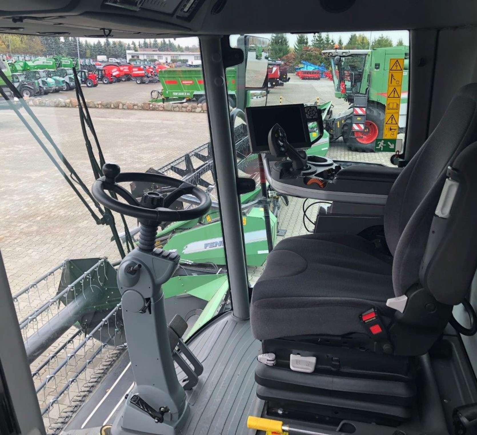 Komfortowe wnętrze kabiny w kombajnie zbożowym 6335 C zdjęcie z lewej strony z widokiem na utwardzony plac maszyn korbanek.pl