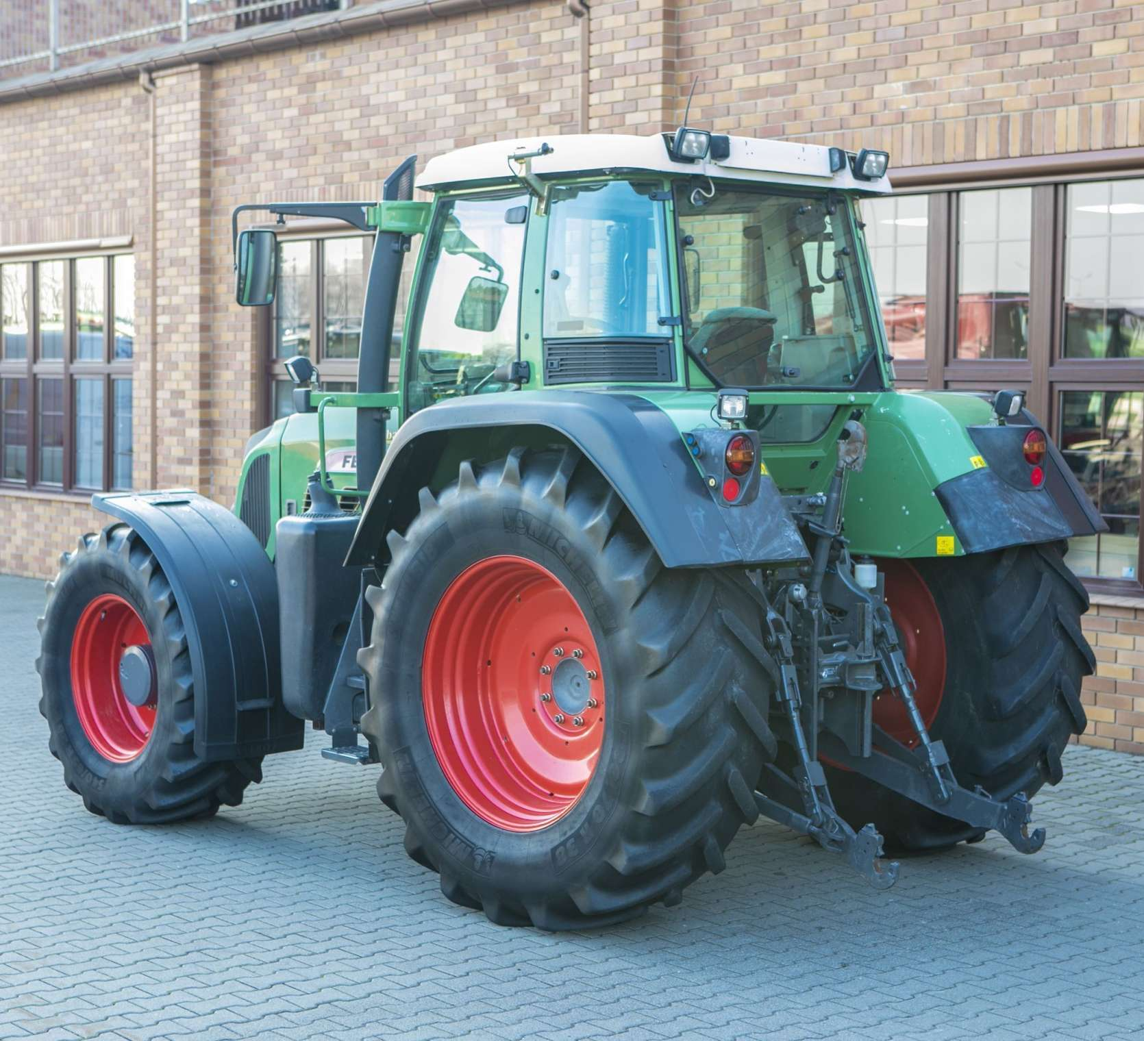 Traktor używany Fendt 716 na tle sklepu Korbanek widok z lewj strony
