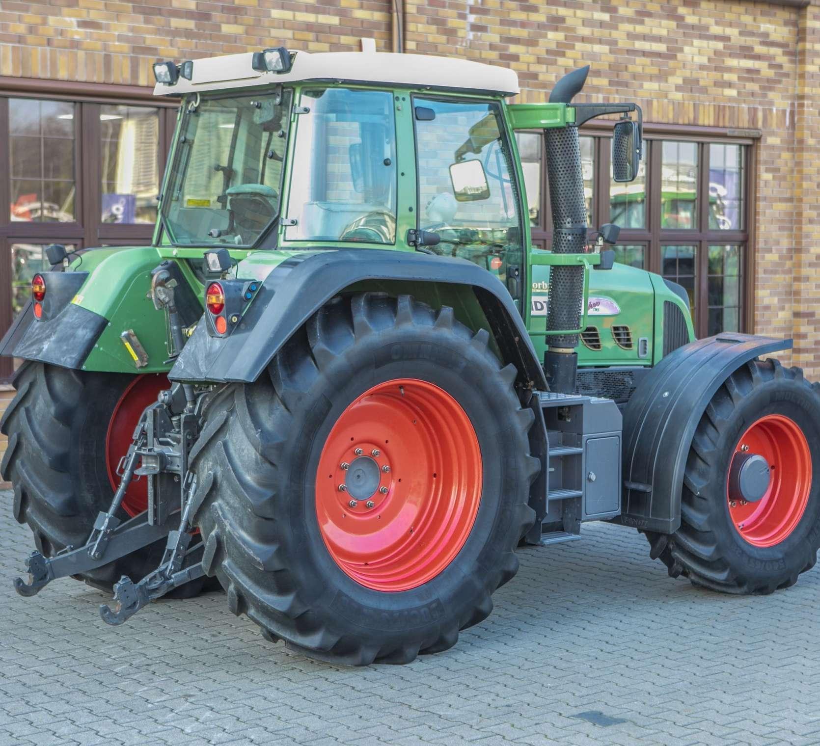 Używany traktor Fendt 716 na tle sklepu Korbanek widok z lewego boku