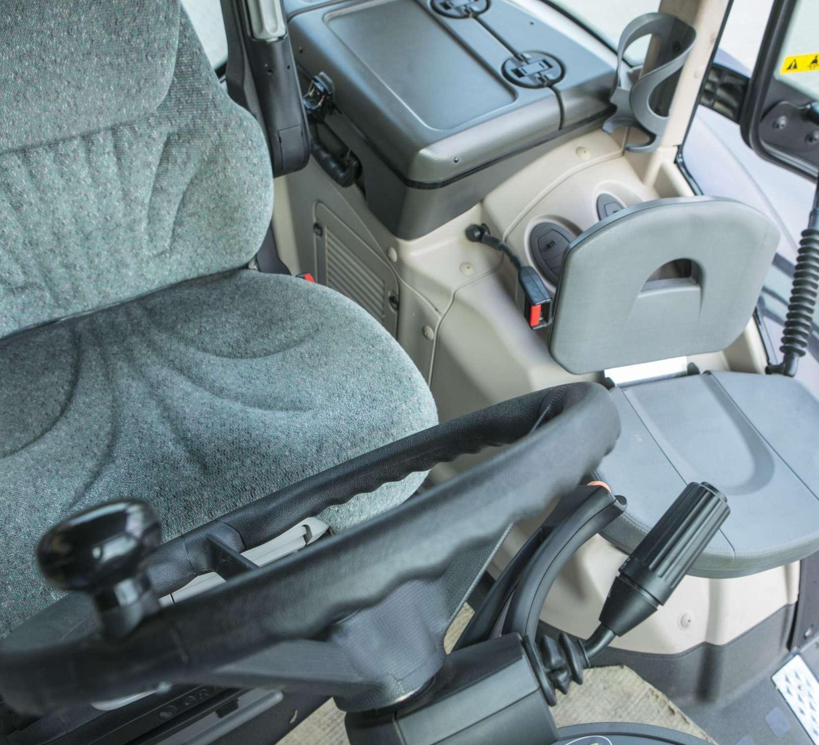 Szary fotel kierowcy i pasażera we wnętrzu kabiny używango ciągnika Fendt 936