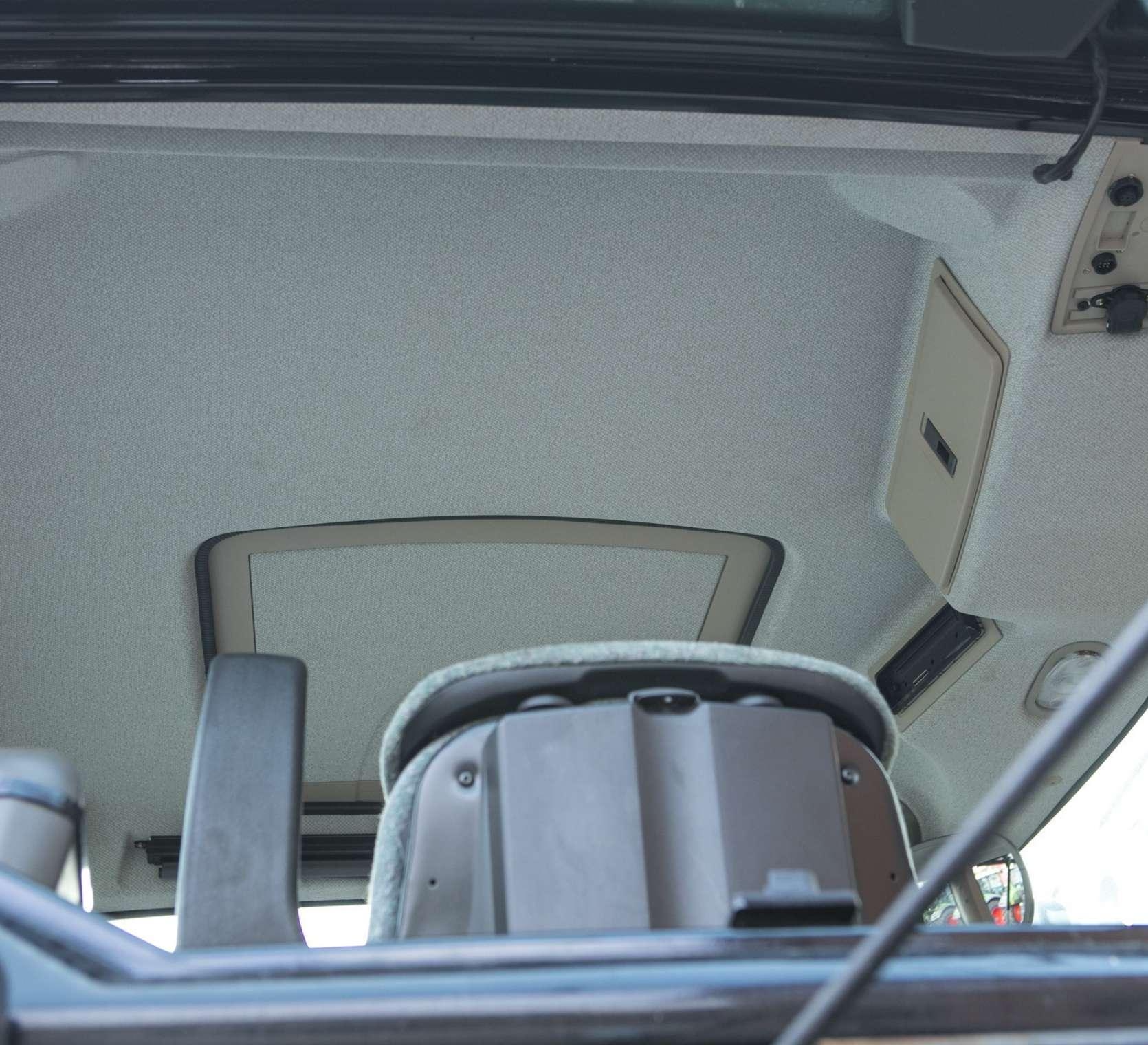 szara sufitówka we wnętrzu komfortowej kabiny używanego ciągnika Fendt 936 Vario
