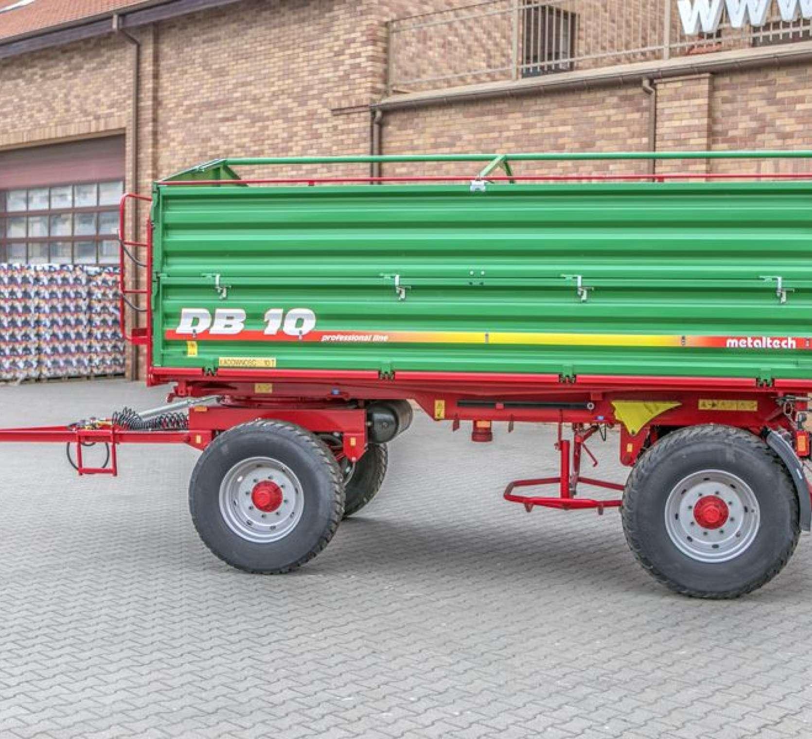 Przyczepa Metaltech DB 10000, skrzynia ładunkowa zielona, rama w kolorze czerwonym, pomost roboczy, koło zapasowe z koszem, dyszel zaczepowy. www.korbanek.pl