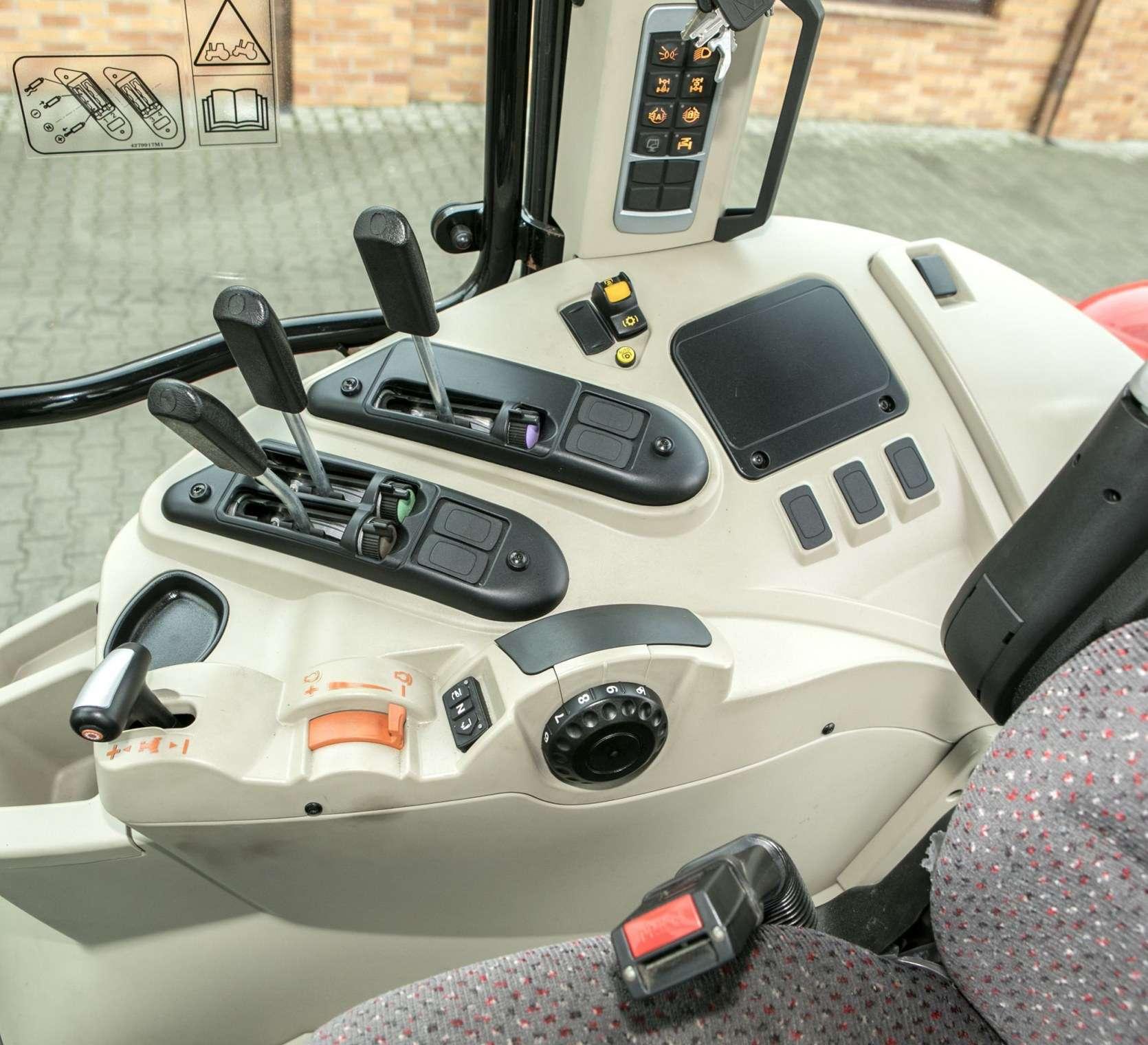 Bok przestronnej kabiny ciągnika MF 5611 kadr przedstawiający dźwignie sterujące