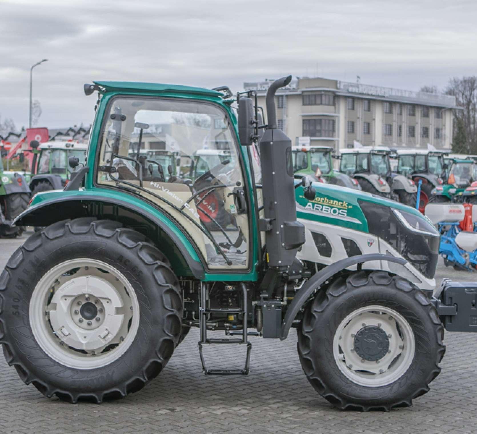 Bok ciągnika arbos 5115 advanced w tle biurowiec korbanek.pl