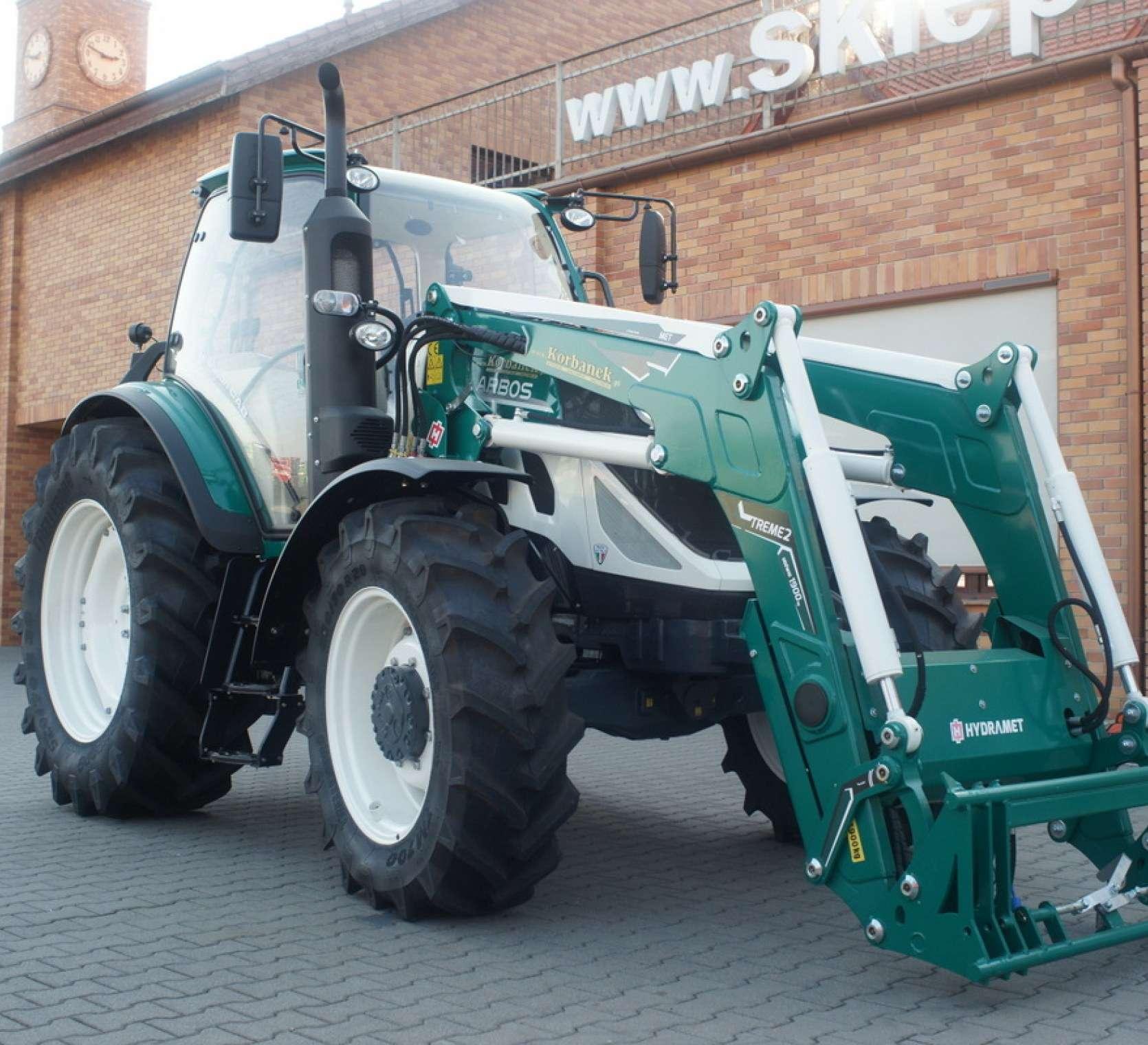 ciagnik arbos 5130 na tle magazynu czesci korbanek zamontowany ladowacz hydramet w kolorze traktora