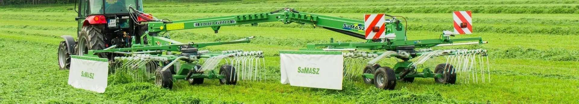 Zielona zgrabiarka zaczepiana 2-gwiazdowa DUO 680 firmy Samasz zaczepiona do czerwonego ciągnika zgrabia trawę na łące Korbanek.pl