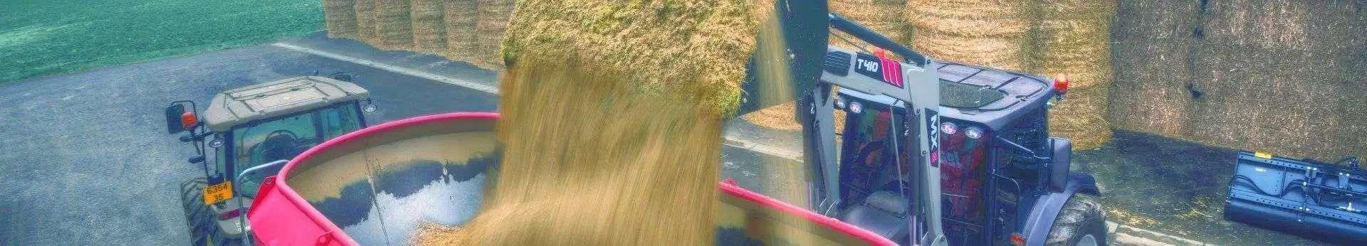 załadunek kiszonki do wozu paszowego ciągnikiem rolniczym z ładowaczem czołowym