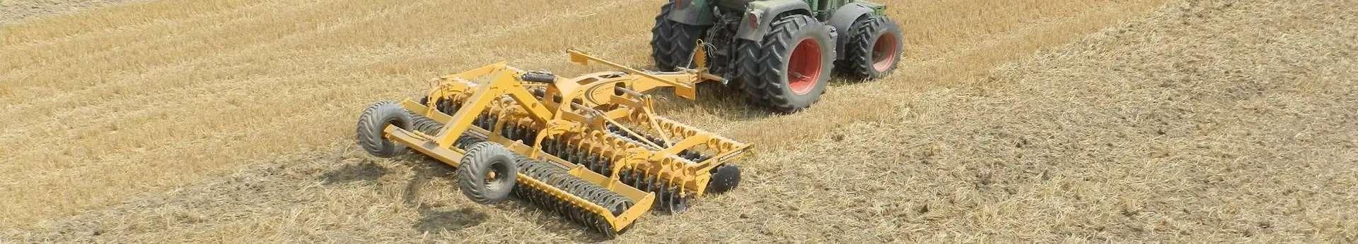Żółty agregat Agrisem Disc-O-Mulch pracuje na polu z ciągnikiem korbanek.pl