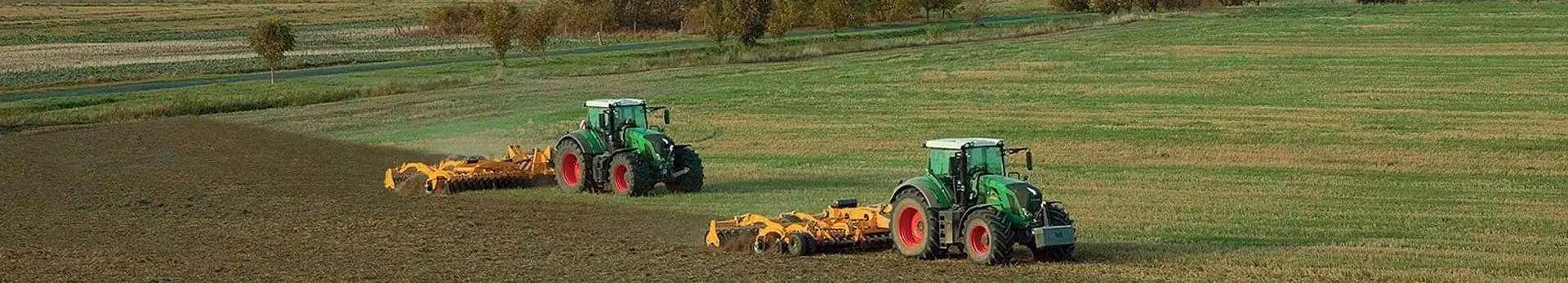 Zdjęcie dwóch agregatów uprawowych AGRISEM pracujących na polu z zielonymi ciągnikami korbanek.pl