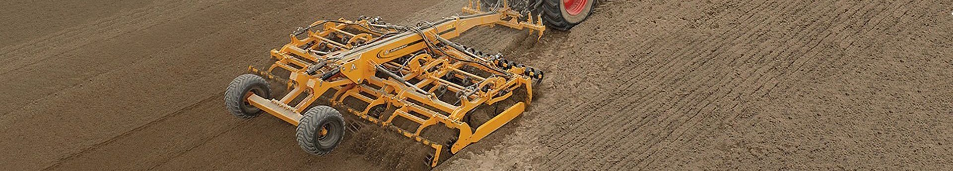 Zdjęcie żółtego agregatu uprawowego cultivator agrisem pracującego na polu korbanek.pl