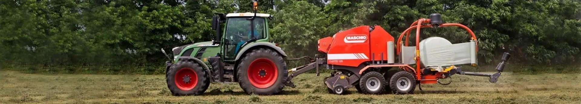 Ciągnik rolniczy ciągnący prasoowijarkę po łące