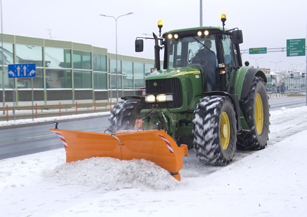 Pług do śniegu PSV firmy Samasz. Pomarańczowy spychacz zawieszony na ciągniku John Deere odśnieża ulicę