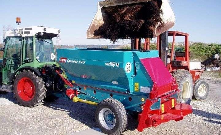 Załadunek rozsiewacza przyczepianego materiałem organicznym za pomocą łyżki ładowacz